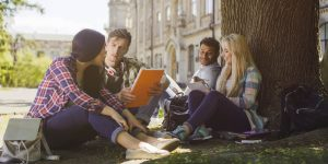 Group of college students sitting outside with textbooks open studying